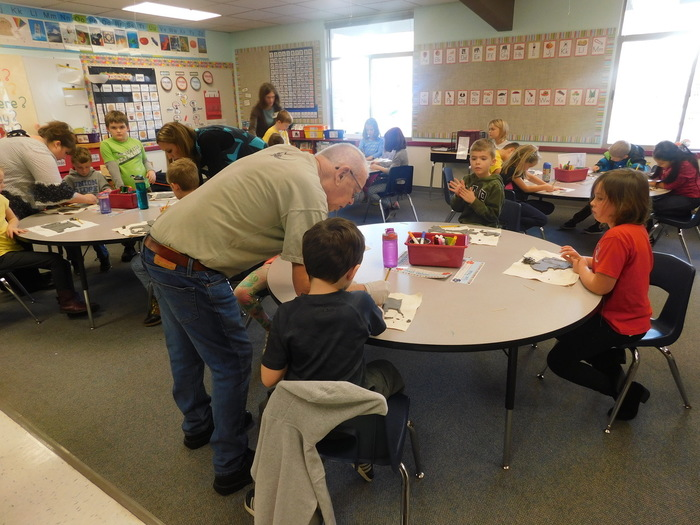 Richard Moody helps UR 2nd graders with Christmas ornament pottery project.