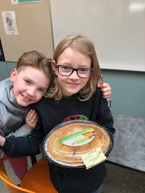 Pi Day Champion Alexa, with her pie and a friend
