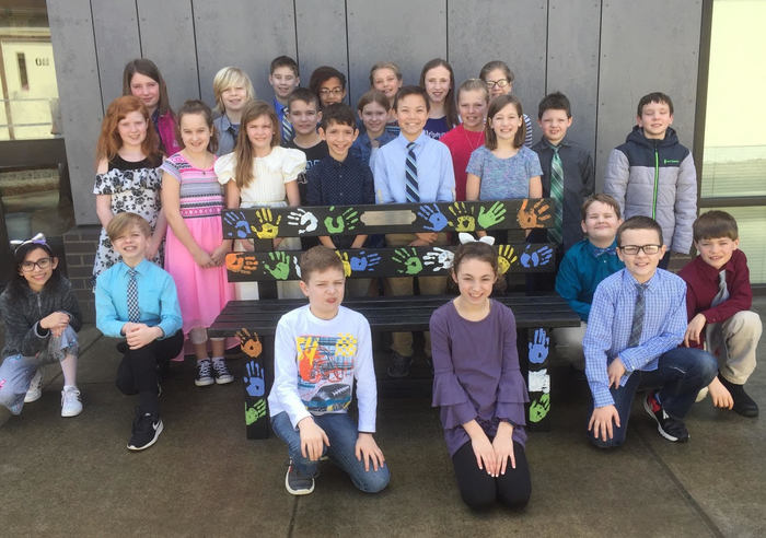 Karen Moses' class stands with the new Friendship Bench