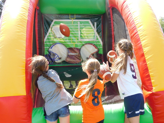 Students compete with a two-sided football pass inflatable.