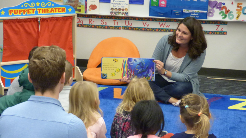 Emily Enquist reads to preschoolers in Mr. Thomas' class at the Early Learning Center.