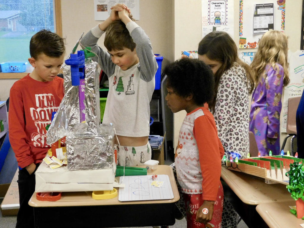 Union Ridge students play with a marble game made from recycled materials
